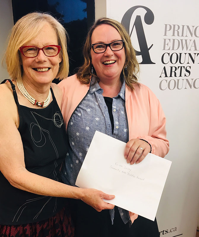 Krista Dalby (right) receives her award from Sarah Moran, Prince Edward County Arts Council